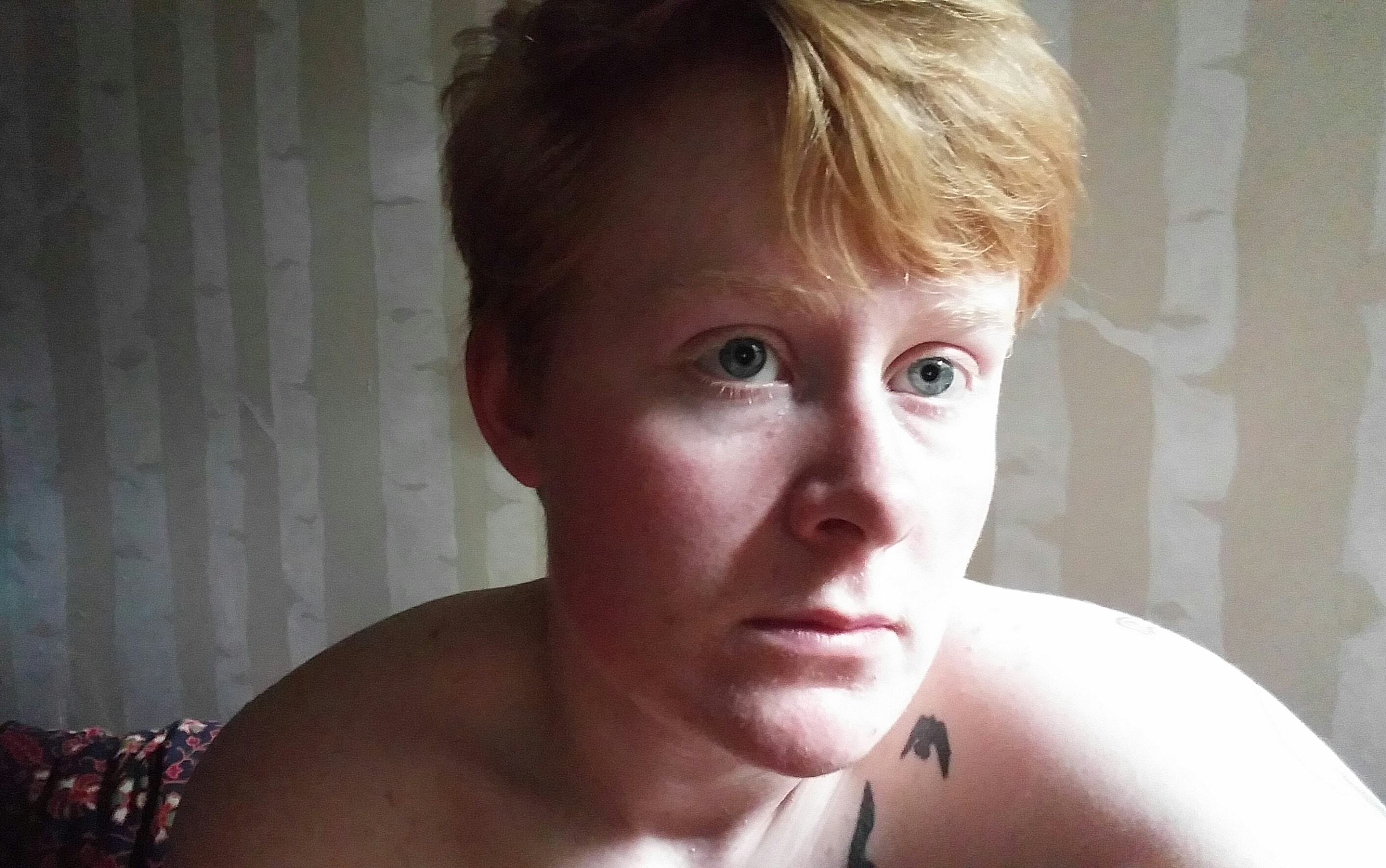 Head-to-shoulders picture of Sage, a non-binary person with short red hair, looking off to the right with a serious expression. Their shoulders are bare and there are birch trees painted on the wall behind them.
