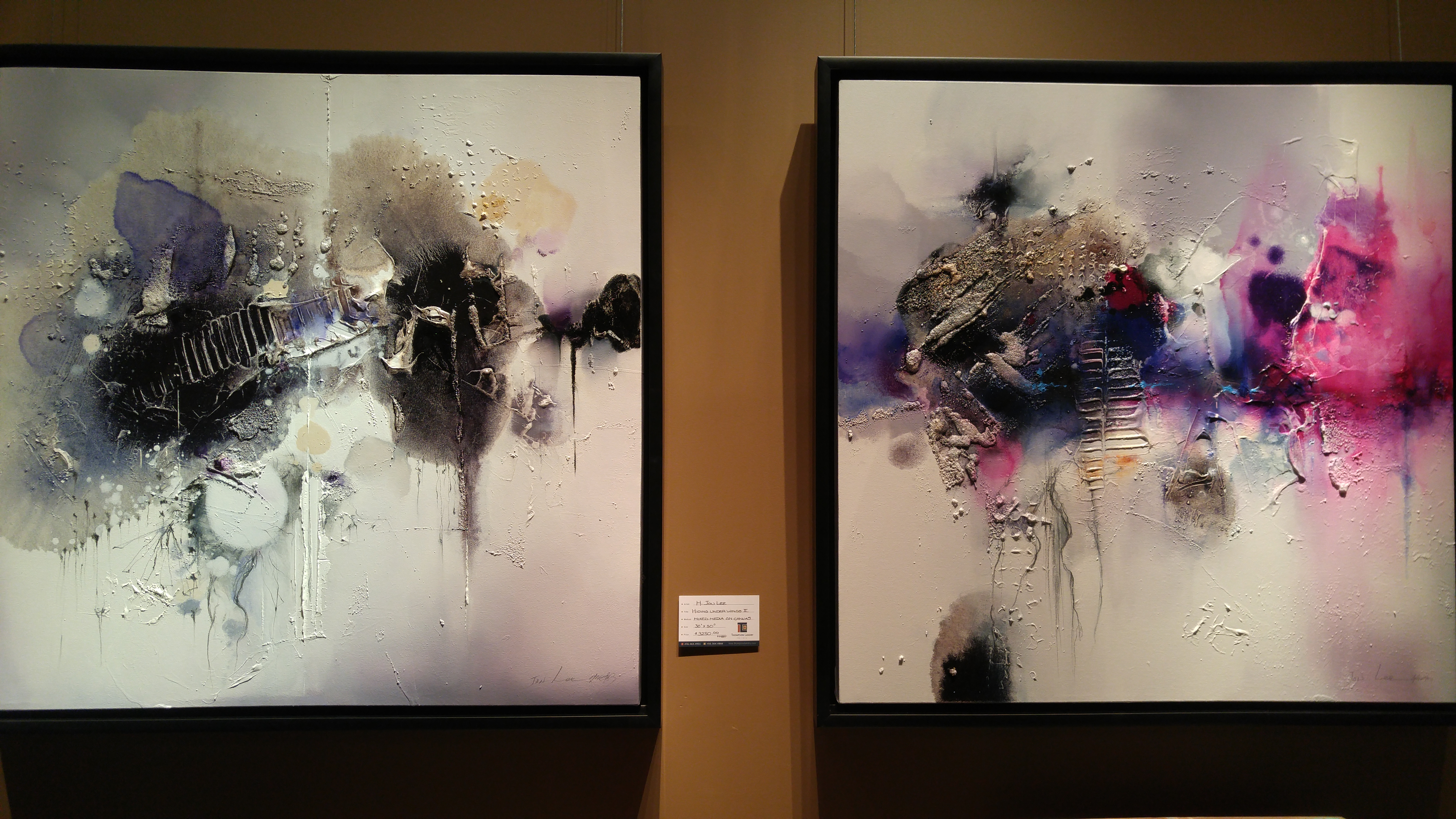 Two abstract paintings with black borders hanging on a yellow wall with an info card between them. The left one has black, grey, purple, and yellow splashes of colour on a white canvas. The right one has black, purple, pink, and yellow splashes of colour on a white canvas.