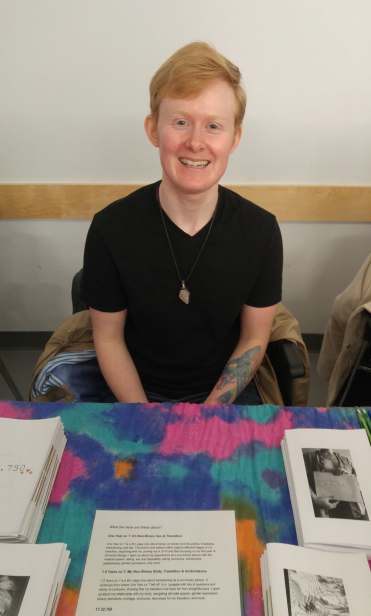 [Image: Sage, a non-binary person with short red hair, sitting at a colourful table in front of stacks of their zines and papers, smiling, wearing a black t-shirt].