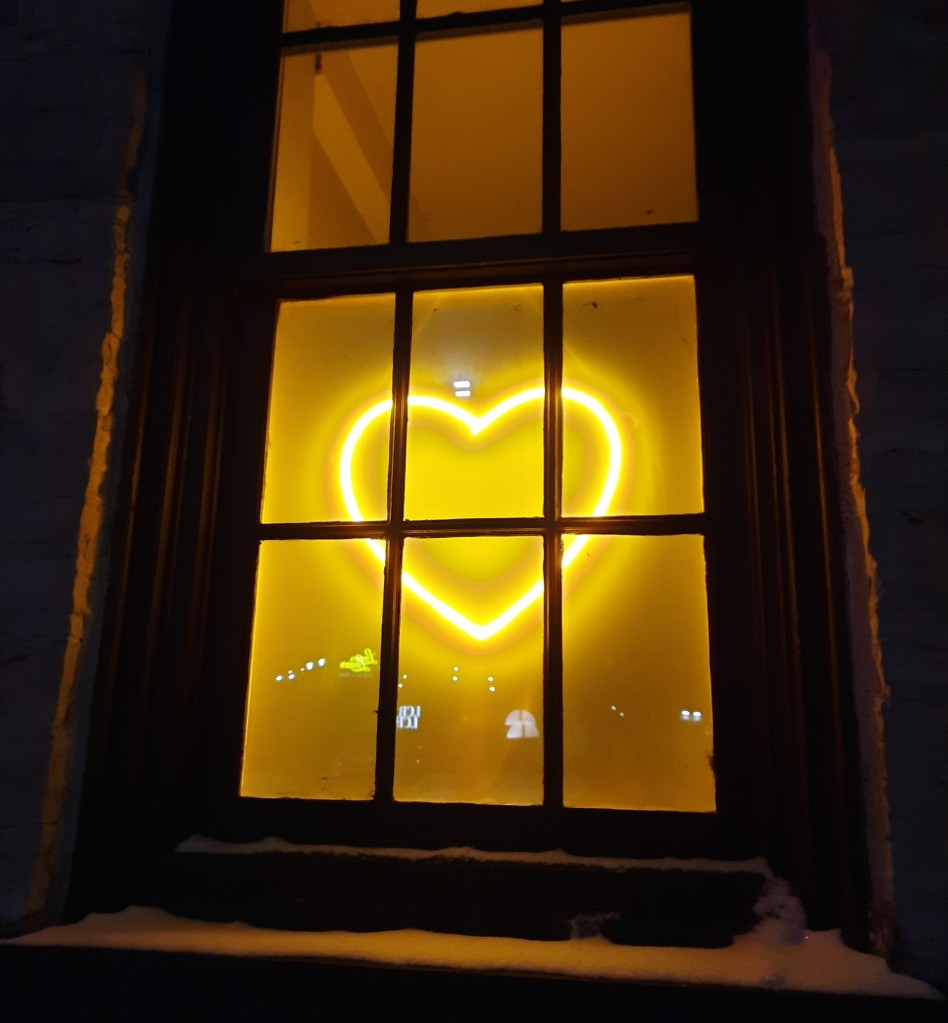 Photograph of a glowing yellow outline of a heart hanging in a window with window panes in front of it. Outdoor window frame with a dusting of snow around the window. It is dark outside and all illumination comes from the heart.