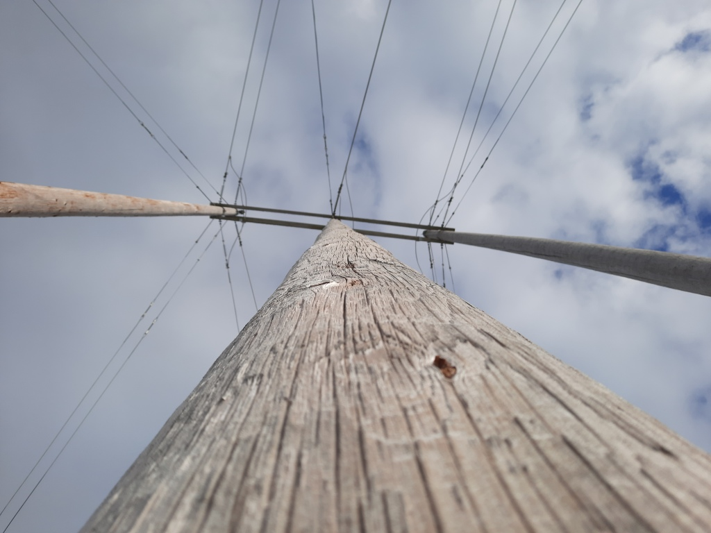Photo of three electrical poles shot from below, with the one in the centre looking like the largest due to the perspective. The three are attached at the top by two pieces of wood and have wires going in all directions from them. A cloudy sky with patches of blue is above.