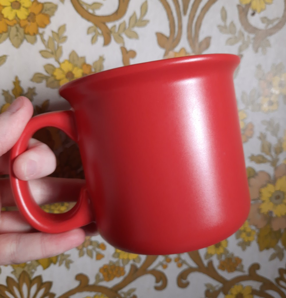 Photo of a wide red mug held by the handle against 70s-style wallpaper with a yellow flower pattern.