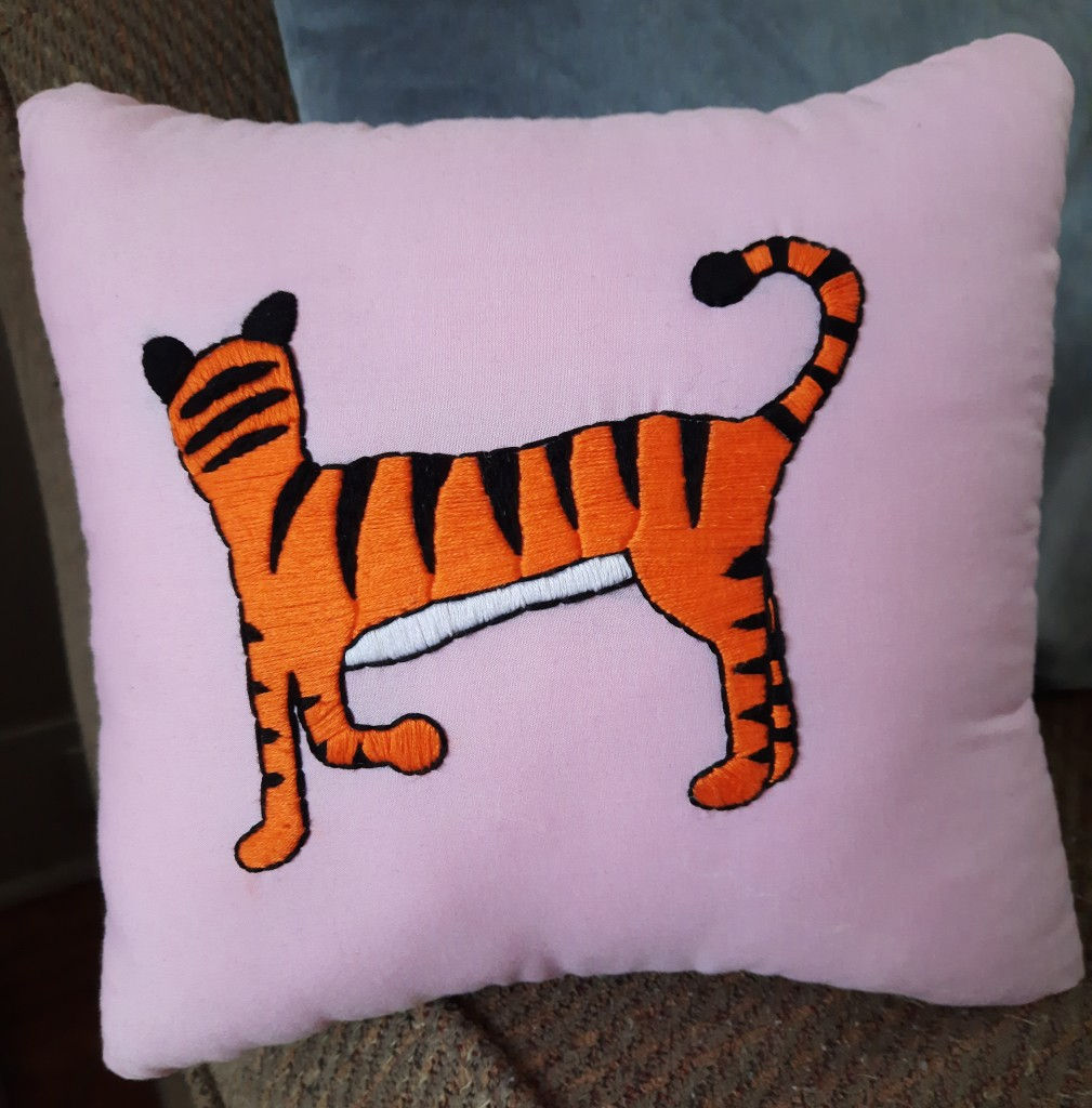 Photo of a pink pillow on a couch with a cartoon tiger stitched on it with a raised front foot and its head turned away.