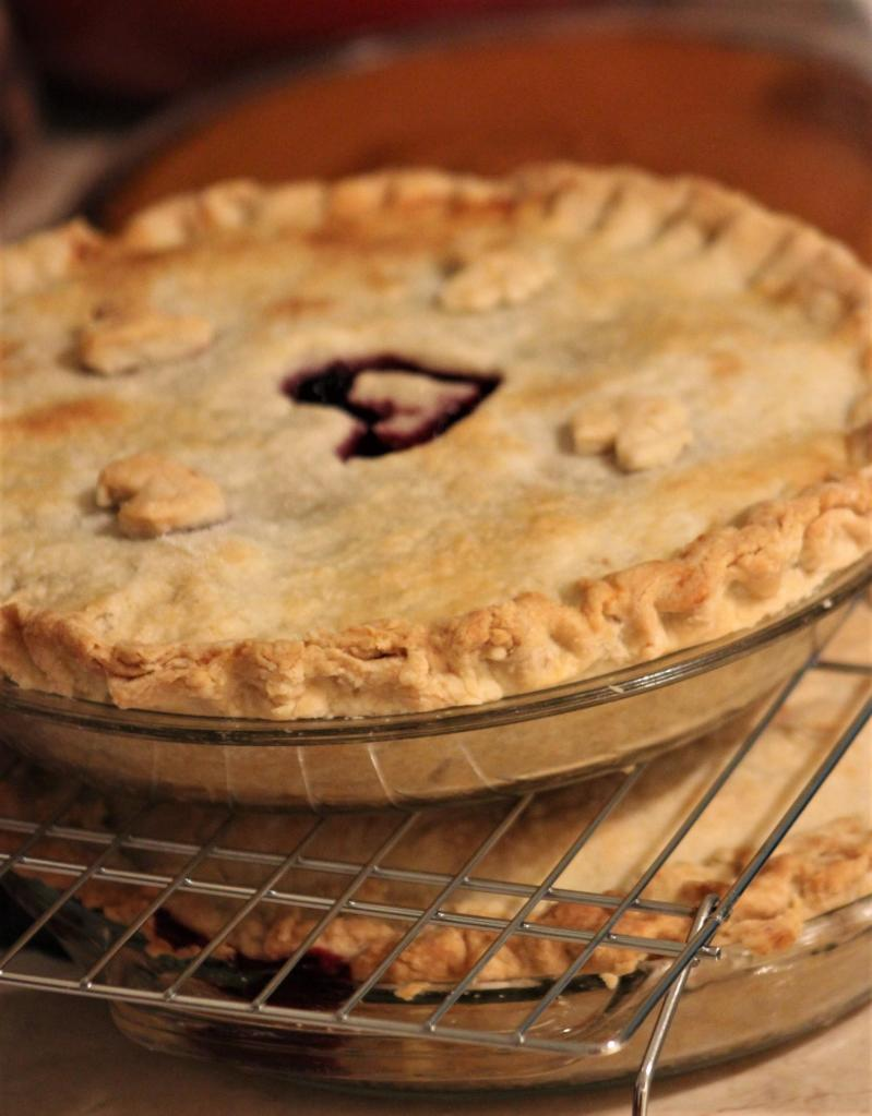 Photo of a cherry pie sitting on a cooling rack with the outline of a heart carved into its centre.