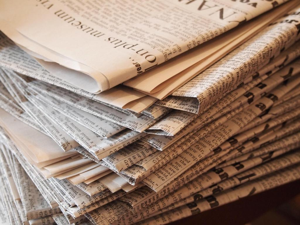 Photo of the corner of a stack of newspapers taken at an angle. Light sepia-coloured filter over image.